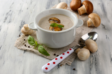 Mushroom soup in white pot, on napkin, on wooden background Stock Photo - 26555172