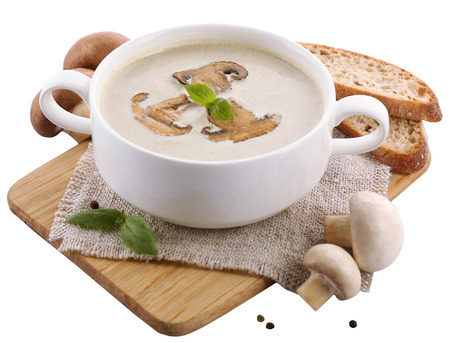 Mushroom soup in white bowl, on napkin, isolated on white photo