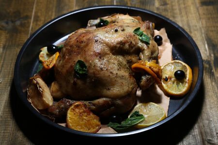 Whole roasted chicken with vegetables on pan, on wooden background Stock Photo - 26555193
