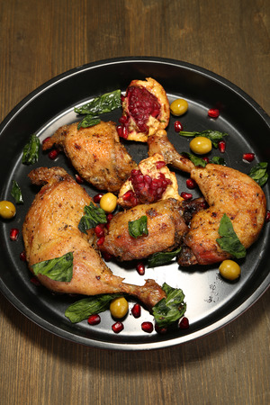 Homemade fried chicken drumsticks with vegetables on pan, on wooden background photo