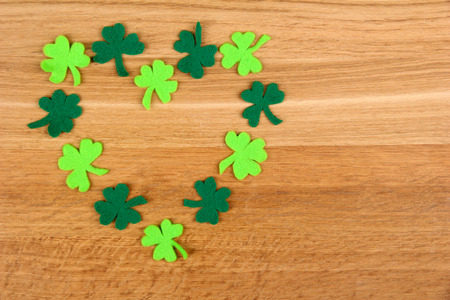 Clover leaves on wooden background photo