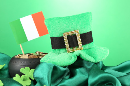 Saint Patrick day hat, pot of gold coins and Irish flag on green background photo