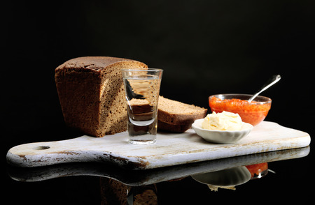 Composition with glasses of vodka, red caviar, fresh bread on wooden board,  isolated on black photo