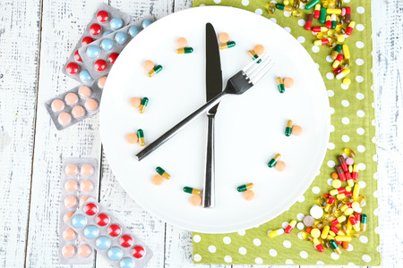 Medication schedule and meals. Conceptual photo. On color napkin, on wooden background photo