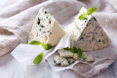 Tasty blue cheese with basil on paper Stock Photo