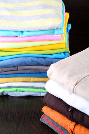 Stack of colorful clothes, on dark background photo