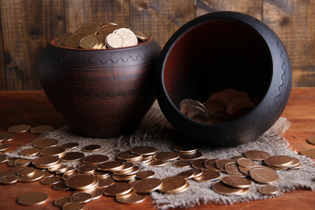 Golden coins in ceramic pots, on wooden background photo