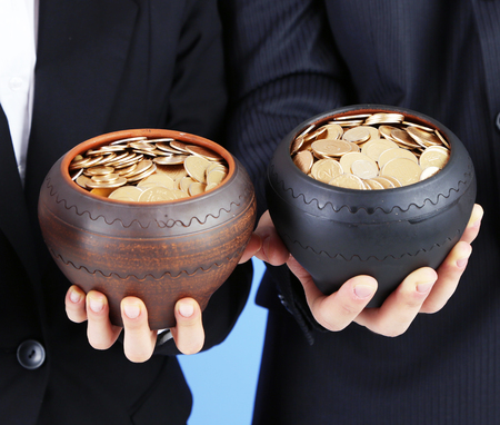Two ceramic pots with golden coins in male and female hands photo