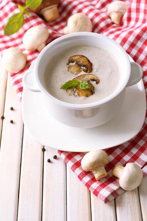 Mushroom soup in white pot, on napkin, on wooden background Stock Photo - 26778854