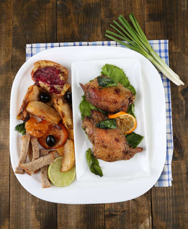 Homemade fried chicken drumsticks with vegetables on plate, on wooden background photo