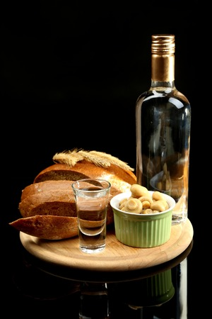 Composition with bottle of vodka, glass, and marinated vegetables on wooden board, isolated on black photo