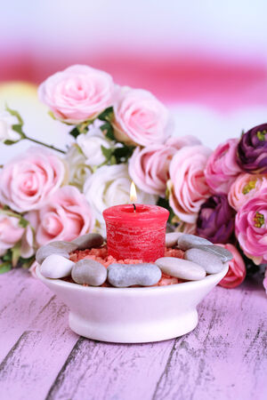 Composition with spa stones, candle  and flowers on color wooden table photo