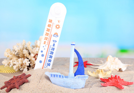 Thermometer  in sand on bright background photo