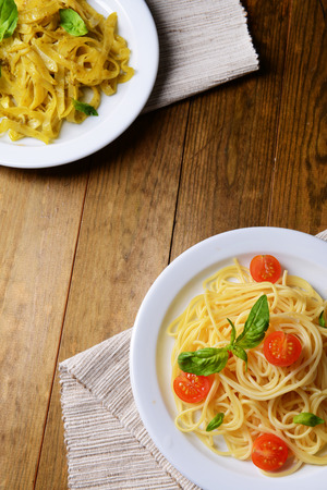 Delicious spaghetti with tomatoes on plate on table close-up photo