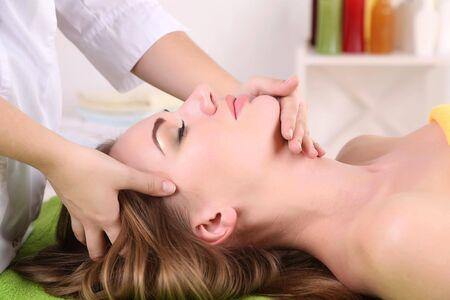 Beautiful young woman having head massage in spa salon