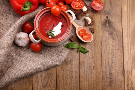 Tasty tomato soup and vegetables on wooden table photo