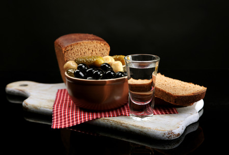 Composition with glasses  of vodka, and marinated  vegetables, fresh bread on wooden board, isolated on black photo