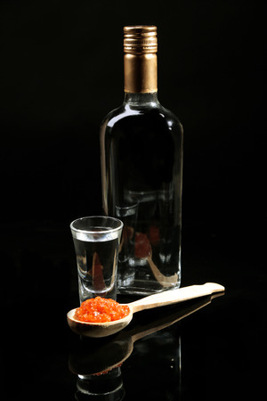 Bottle of vodka, red caviar  isolated on black photo