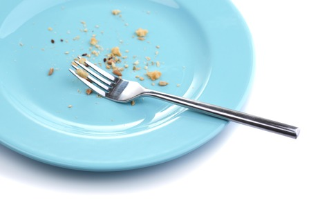 Plate with crumbs and used fork, close-up, on white background photo