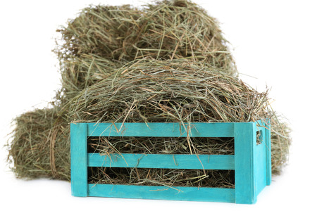 Hay in wooden crate, isolated on white photo