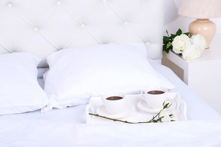daily room: Cups of coffee on comfortable soft bed with pillows Stock Photo