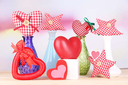 Hand-made textile hearts in different vases on wooden table, on light background photo