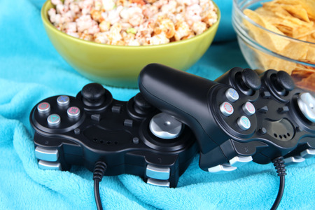 Black game controllers and bowl with snacks on color plaid background photo