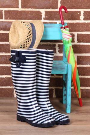 Composition with pair of colorful gumboots, chair, hat, umbrella on color wall background photo