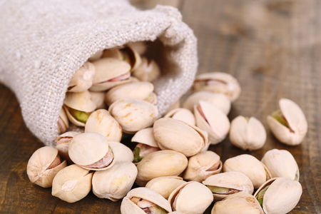 Pistachio nuts in sackcloth bag on wooden background photo