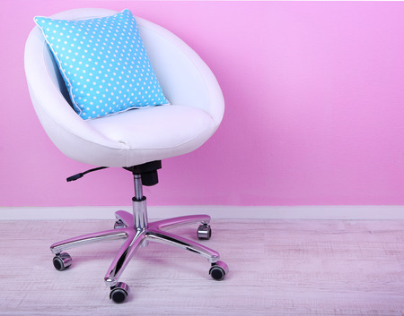 Modern chair in room on pink background photo