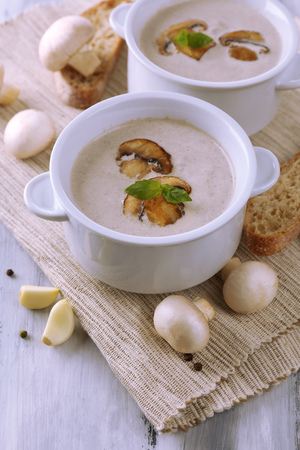 Mushroom soup in white pots, on napkin,  on wooden background Stock Photo - 26980795
