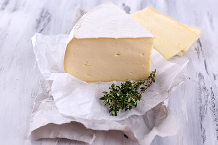 chees: Tasty Camembert cheese with thyme, on wooden table Stock Photo