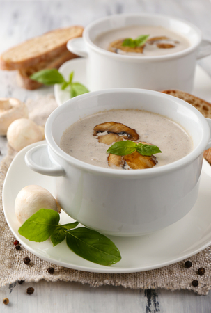 Mushroom soup in white pots, on napkin, on wooden background Stock Photo - 26981036