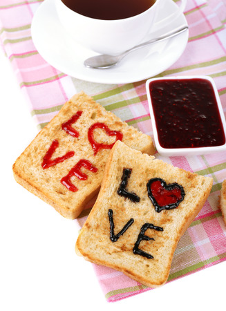 Delicious toast with jam and cup of tea on table close-up photo