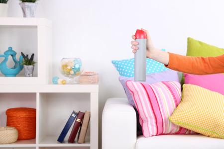 Sprayed air freshener in hand on home interior background photo
