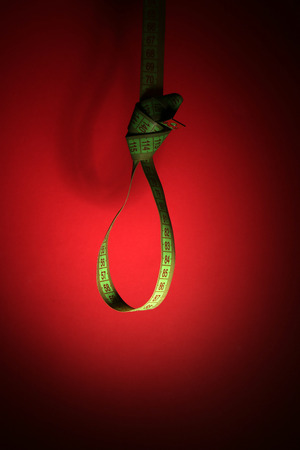 Tape measure noose on red background - diet concept photo