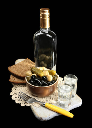 Composition with bottle  of vodka, and marinated  vegetables, fresh bread on wooden board, isolated on black photo