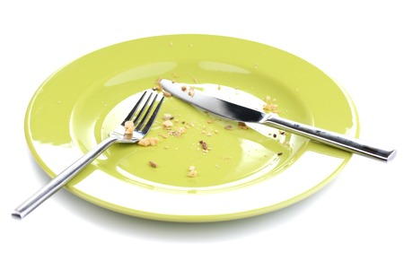 Plate with crumbs and used fork and knife, close-up, on white background photo