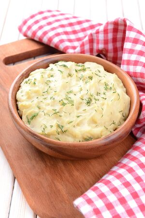 Delicious mashed potatoes with greens in bowl on table close-up photo