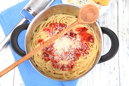 Composition with tasty spaghetti in pan, grater, cheese, on wooden table background photo