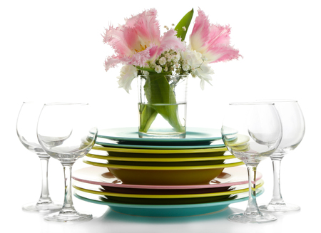 Stack of colorful ceramic dishes and flowers, isolated on white photo