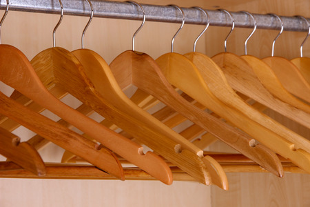 Wooden hangers in wardrobe photo