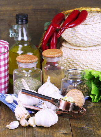 Composition with garlic press, fresh garlic and glass jars with spices on wooden  photo