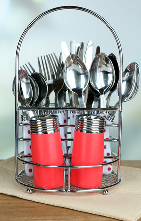 Kitchen cutlery in metal stand on wooden table on bright  photo