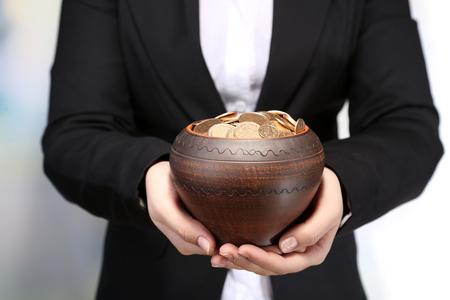 m�nzenwerfen: Keramik-Topf mit goldenen M�nzen in weiblichen H�nden, auf hell