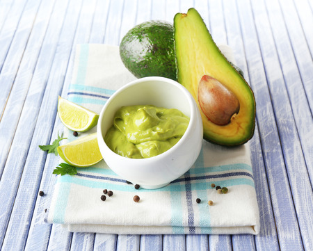 guacamole: Fresh guacamole in bowl on wooden table