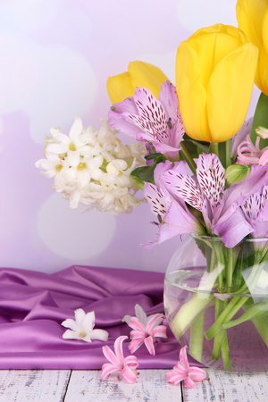Flowers in vase on table on bright  photo