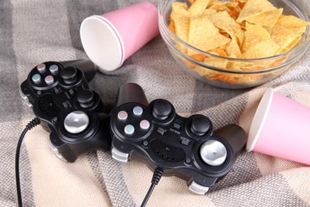 bowl game: Black game controllers and bowl with snacks on color plaid background