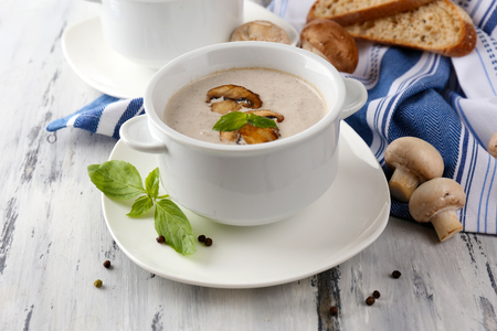 Mushroom soup in white pots, on napkin, on wooden background photo