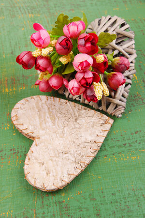 Decorative hearts and flowers  on color wooden background photo